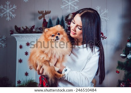 Girl with a Dog on the Background of New Year's Decoration. Fashion Beauty Portrait. Sexy Girl. Holiday Makeup