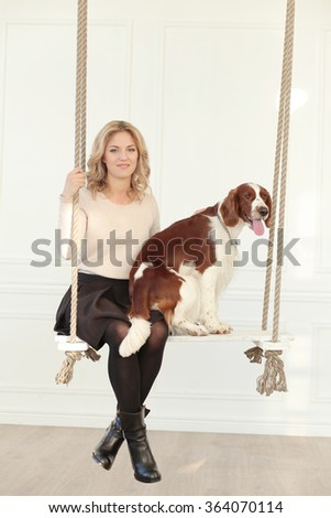 Girl with a dog on the swing - stock photo