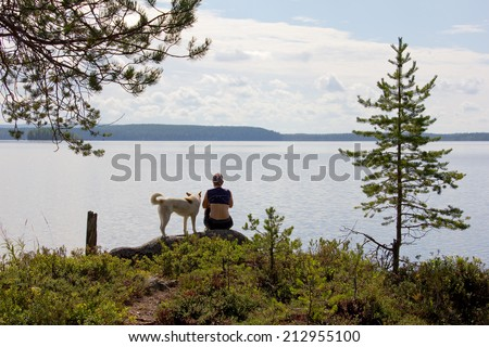 girl with a dog sitting on a rock at the lake, the view from the back, Russia, Karelia, 2014 - stock photo