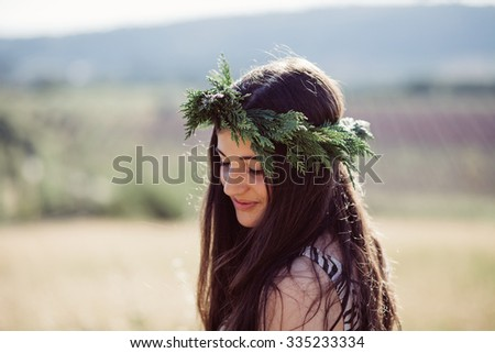 Girl with a flower garland on a field on a beautiful summer day - stock photo
