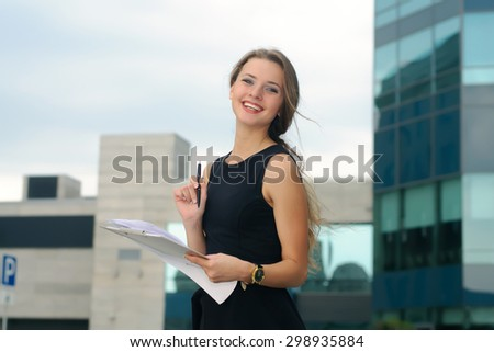 Girl with a folder for papers in her hands cheerfully laughs against a background of modern buildings - stock photo