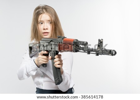 Girl with a frightened look with a Kalashnikov in his hand. Isolated