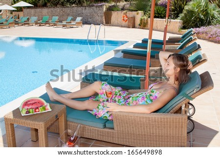 Girl with a glass of champagne on a sunbed by the pool. In the summer on vacation. - stock photo