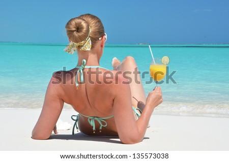 Girl with a glass of orange on the beach of Exuma, Bahamas - stock photo