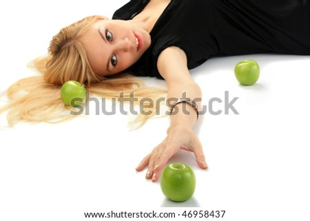 Girl with a green apple lies on the isolated background. Focusing on apple - stock photo