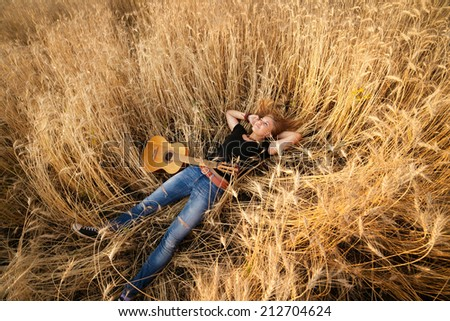 girl with a guitar lying in the wheat field, view from above - stock photo