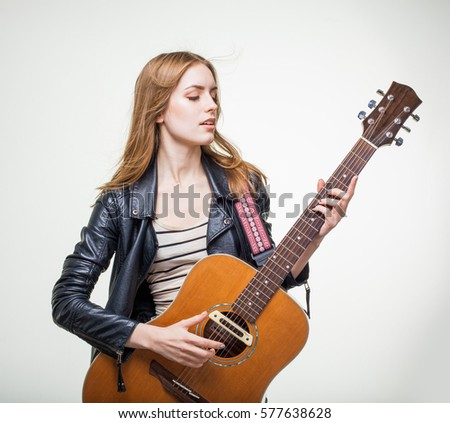 girl with a guitar on a white background, young woman playing acoustic guitar rock, leather jacket, long hair, wind, smile, blonde girl plays music, learn to play guitar.