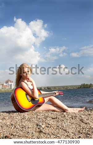 girl with a guitar on the waterfront