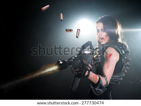 Girl with a gun goes on the attack - stock photo
