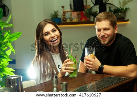 Girl with a guy at the bar laughing and drinking alcoholic cocktails