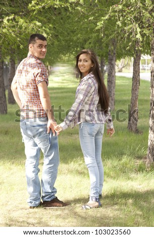 Girl with a guy in a checkered shirt and blue jeans walking in the park among the rows of trees, holding hands and looking at each other - stock photo