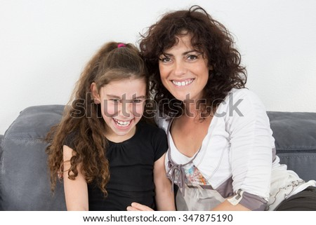 Girl with a  happy mom at home smiling