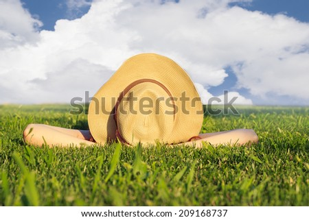 Girl with a hat, lying in the grass, enjoying sunny summer day. No visible face