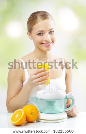 Girl with a juicer and orange juice on a light background - stock photo
