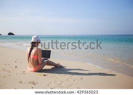Girl with a laptop on the beach in Thailand