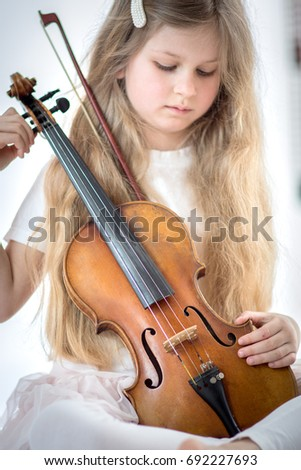 Girl with a long blond hair holding a violin