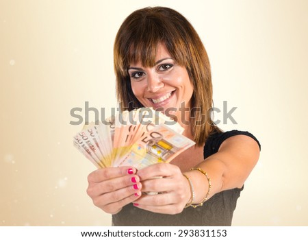 Girl with a lot of money over ocher background