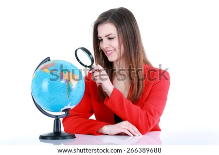 Girl with a magnifying  loupe looking at the globe. Isolated on white background - stock photo
