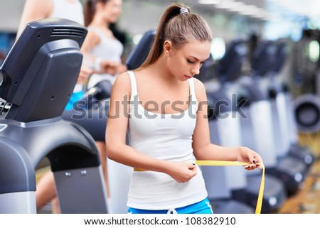 Girl with a measuring tape in fitness club - stock photo