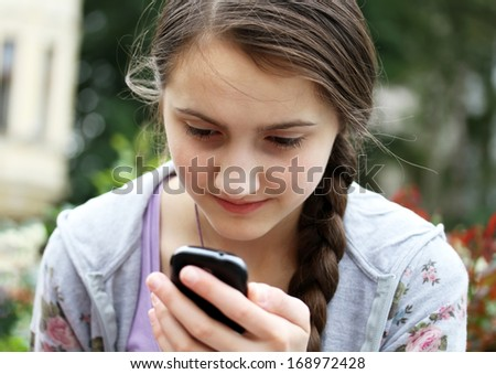 Girl with a mobile phone reads the message - stock photo