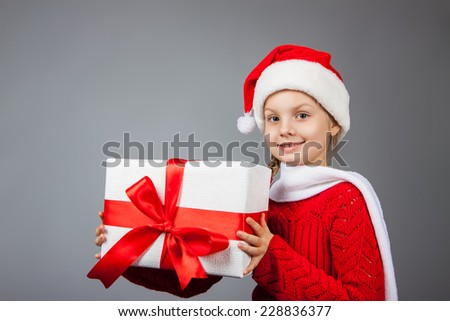 girl with a New Year gift. Joyful girl in a cap of Santa Claus