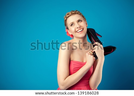 Girl with a pair of new shoes isolated on blue background - stock photo