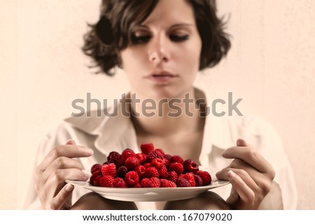 Girl with a plate full of raspberries - stock photo