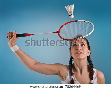 girl with a racket in hands on a blue background.playing a badminton.sport.active rest. - stock photo