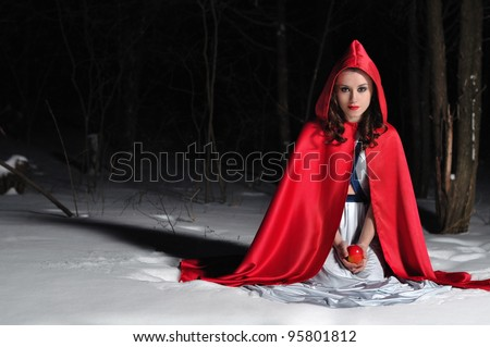 Girl with a red cloak sitting in the snow at night