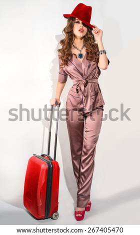 Girl with a red suitcase in a beautiful dress, a red hat. - stock photo