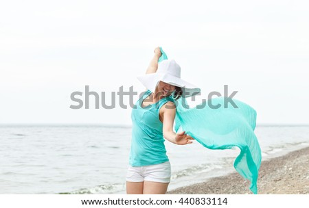 girl with a scarf on the beach enjoying life.