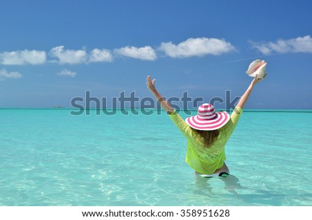 Girl with a seashell in the turqouise water of Atlantic. Exuma, Bahamas - stock photo