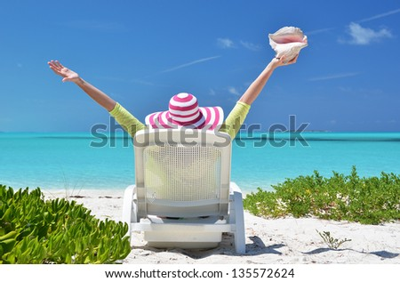 Girl with a shell on the sunbed looking to the ocean. Exuma, Bahamas - stock photo