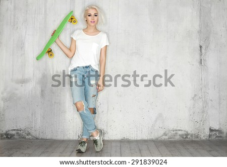 Girl with a skateboard in his hand against the background of a concrete wall - stock photo