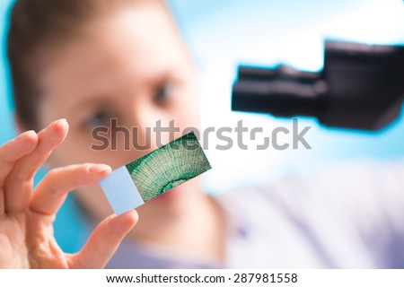 Girl with a slide for the microscope University Hospital