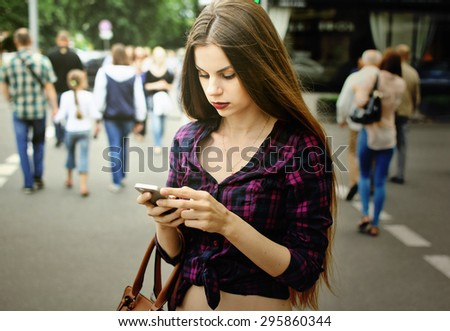 Girl with a smart-phone standing at a crosswalk - stock photo