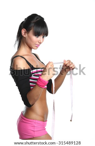 girl with a sports figure looks on measuring tape  - stock photo