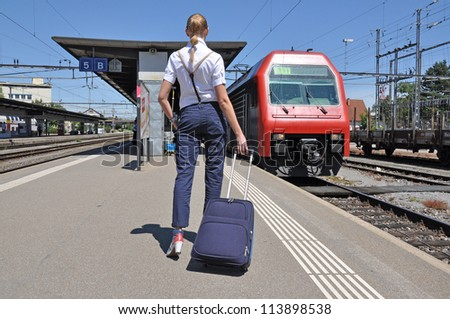 Girl with a suitcase at the train station - stock photo