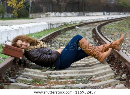 Girl with a suitcase lying on the tracks