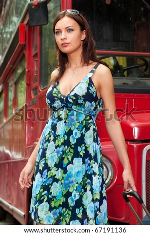 Girl with a suitcase on the background of a red bus