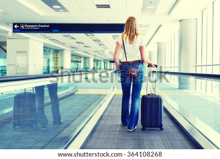Girl with a suitcase on the speedwalk - stock photo