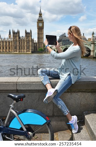 Girl with a tablet against UK Parliament - stock photo