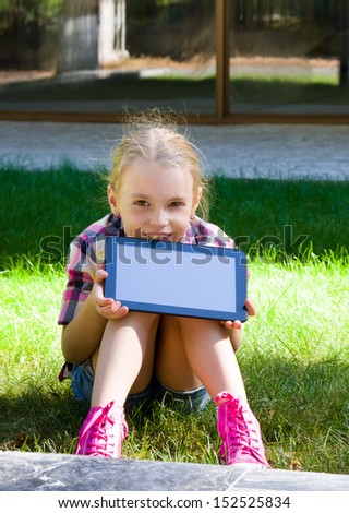 Girl with a tablet in hands near the school building. - stock photo