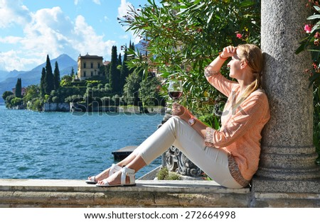 Girl with a wineglass at the Como lake, Italy  - stock photo