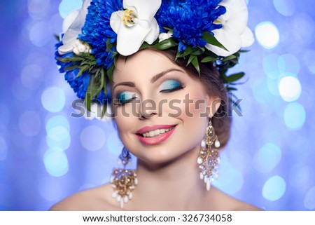 Girl with a wreath of flowers on her head on a blue background of blue lights. bokeh, background, blur. Young smiling woman with bright makeup. Earrings