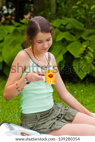 Girl with a yellow cup outdoors, sitting - stock photo
