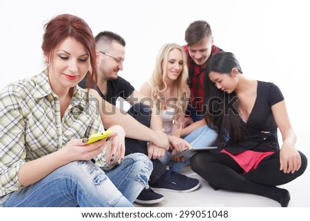 girl with a yellow mobile phone sitting on the floor with a group of students with the tablet