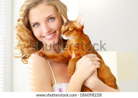 girl with Abyssinian cat on light background - stock photo
