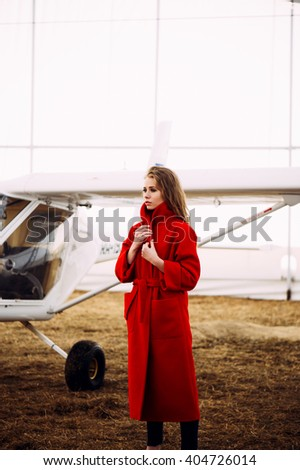 girl with aircraft in coat - stock photo