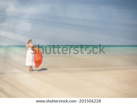 Girl with an orange umbrella on the sandy beach  - stock photo